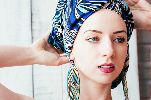 A pretty woman in a blue headscarf in an african manner