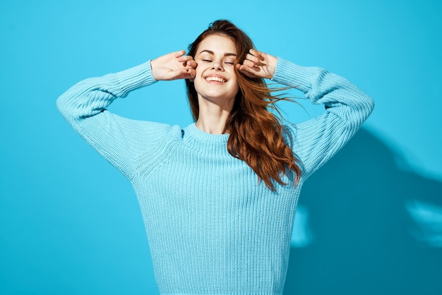 Pretty woman in blue sweater gesturing with hands emotions casual clothes studio blue background. high quality photo