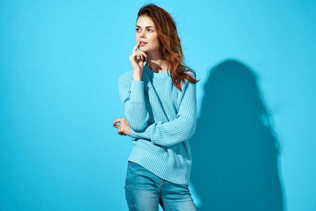 Pretty woman in blue sweater and jeans shadow on  wall.