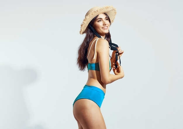 Pretty woman in blue swimsuit beach hat summer lifestyle light background