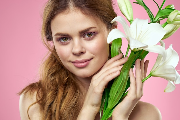 예쁜 여자 꽃다발 꽃 매력 맨 손으로 어깨 근접 분홍색 배경. 고품질 사진