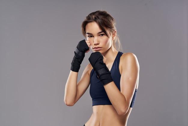 きれいな女性のボクシングのトレーニングは、暗い背景のポーズでフィットネスを練習します