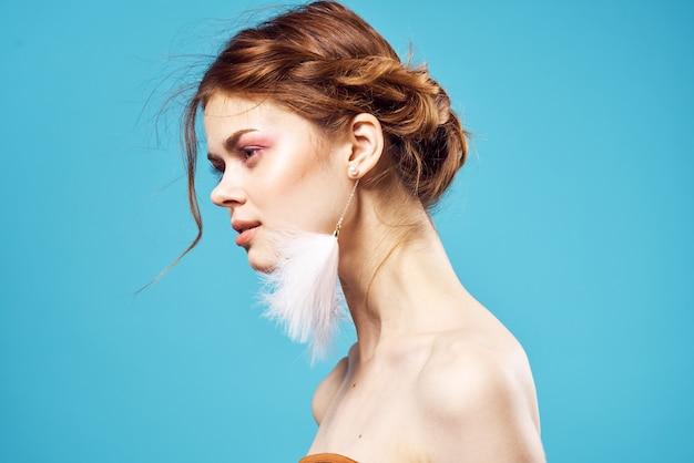 きれいな女性の明るいメイクの装飾ヌード肩ファッション青い背景。高品質の写真