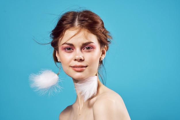 Pretty woman bright makeup decoration nude shoulders fashion blue background