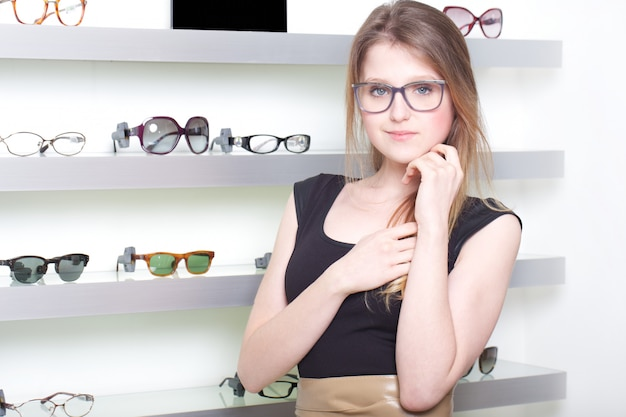 Pretty woman buying new pair of eyeglasses
