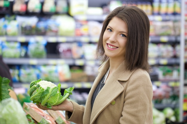Pretty woman buys at supermarket