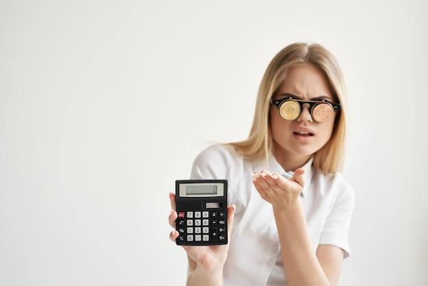 手とビットコインの明るい背景のきれいな女性の計算機