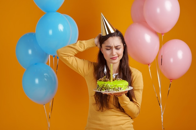 Pretty woman in cap holding birthday cake with firework, yellow background. smiling male person got a surprise, event celebration, balloons decoration