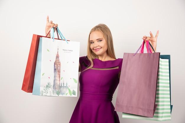 ショッピングバッグの束を運ぶきれいな女性。