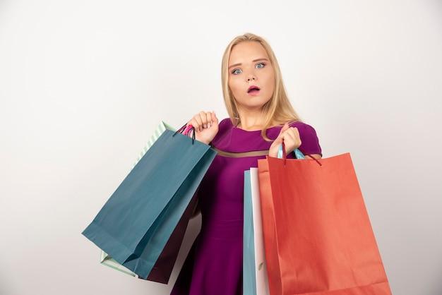 困惑した表情でカラフルな買い物袋を運ぶきれいな女性。