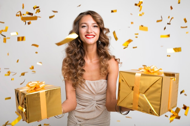 Pretty woman celebrating new year holding presents