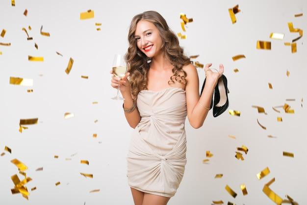 Красивая женщина празднует новый год в золотом конфетти