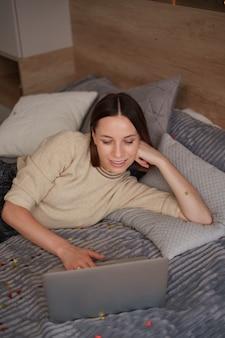 ノートパソコンを使用してオンラインで家族や友人と祝い、ベッドで紙吹雪とコーヒーを飲むきれいな女性