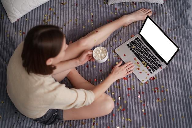 Bella donna che celebra con la sua famiglia e gli amici online utilizzando il laptop, bevendo caffè con coriandoli sul letto