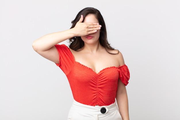 片手で目を覆っているきれいな女性は、恐怖や不安を感じ、不思議に思ったり、盲目的に驚きを待っています