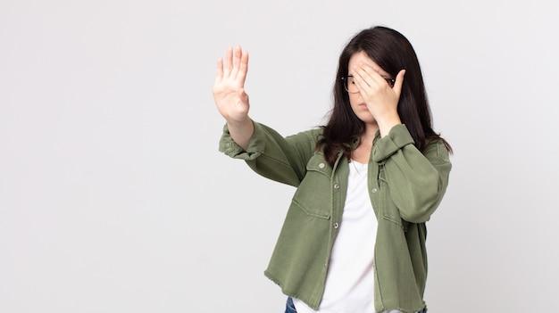 예쁜 여자는 손으로 얼굴을 가리고 다른 손을 앞에 두고 카메라를 멈추고 사진이나 사진을 거부합니다.