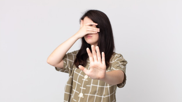 Pretty woman covering face with hand and putting other hand up front to stop camera, refusing photos or pictures