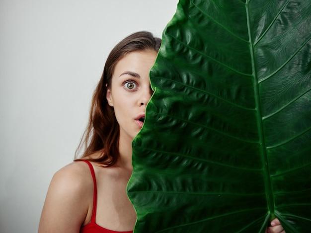 きれいな女性は彼女の顔の半分を緑の葉の光の背景スタジオで覆います