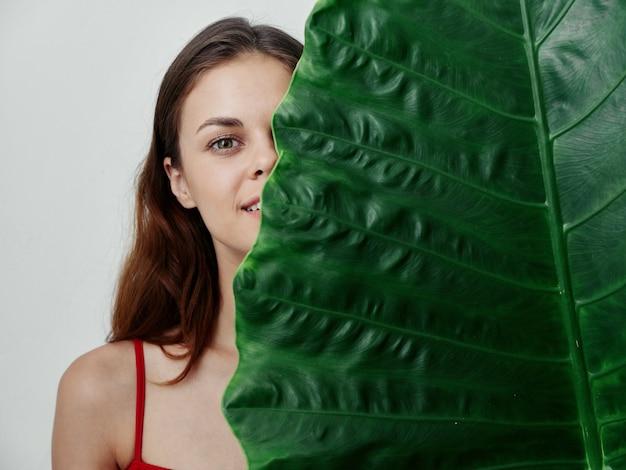 きれいな女性が大きな緑の葉のクローズアップスタジオで顔の半分を覆っている