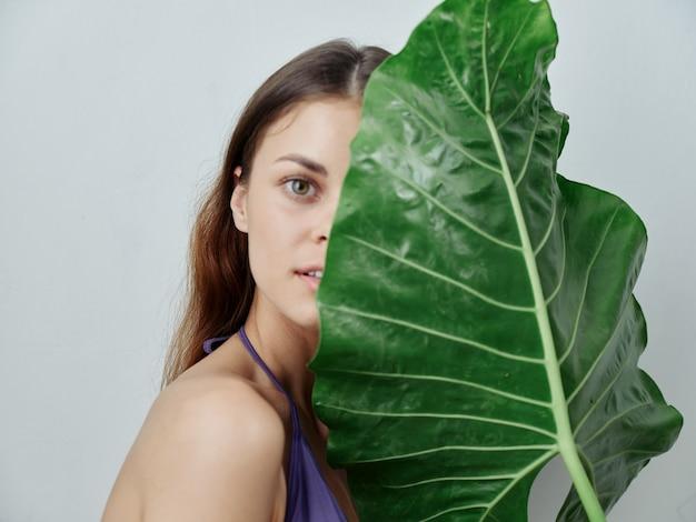 きれいな女性は彼女の顔の半分を緑の葉の水着のトリミングされたビューで覆います