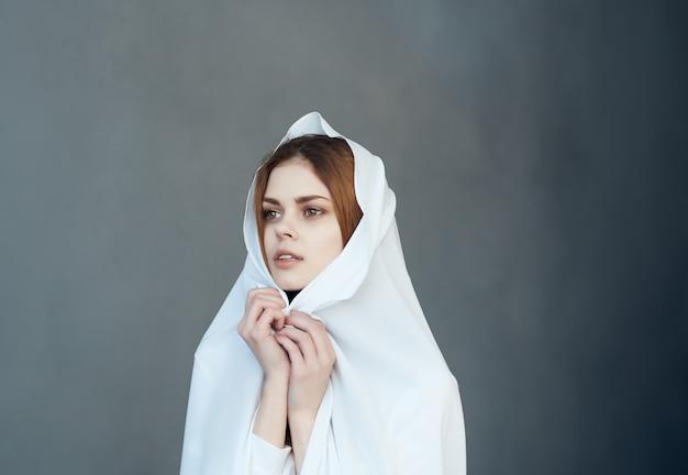 예쁜 여자는 머리 화장 패션 스튜디오와 함께 흰색 천으로 자신을 덮습니다