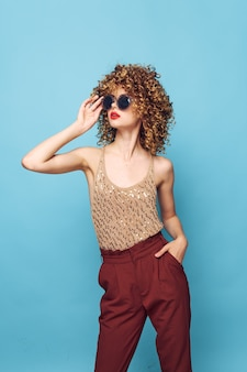 Pretty woman curly hair sunglasses fashion clothes red pants cropped view