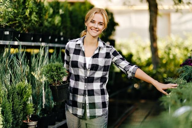 Bella donna in abiti carini che raggiungono per le piante in serra
