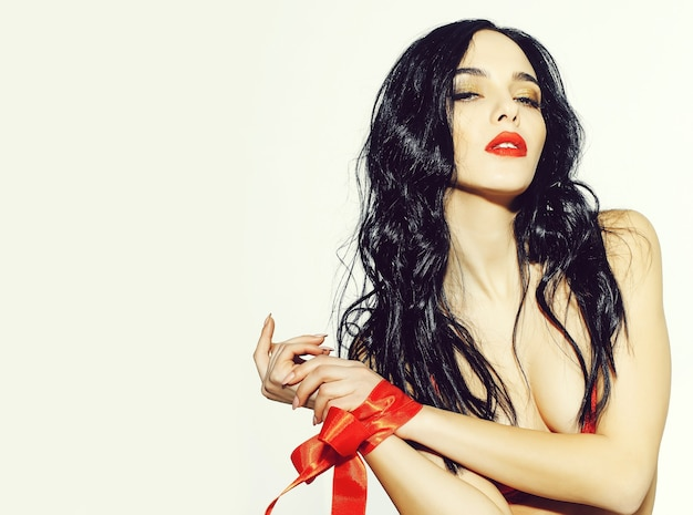 Pretty woman or cute sexy girl in erotic bra with long curly brunette hair, has red lips, makeup on adorable face and ribbon bow on hands isolated on white background, copy space