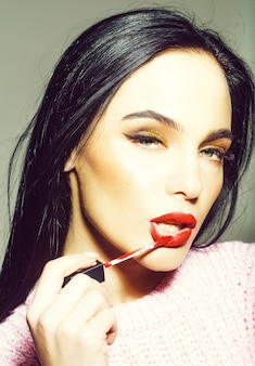 Pretty woman or cute sexy girl with long curly brunette hair, has red lips, makeup on adorable face holds lipstick brush near mouth on grey background