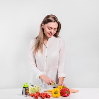 Pretty woman cutting yellow pepper on wooden board