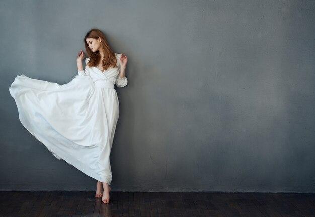 어두운 배경에서 흰 드레스를 입고 춤추는 예쁜 여자