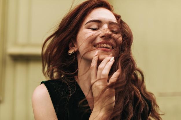 Pretty woman in dark green top smiling outside