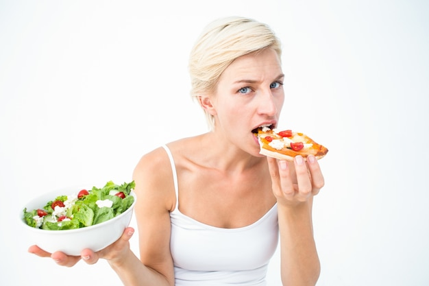 Pretty woman deciding eating pizza rather the salad