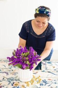 美しいフラワーアレンジメントで彼女の家のテーブルを飾るきれいな女性