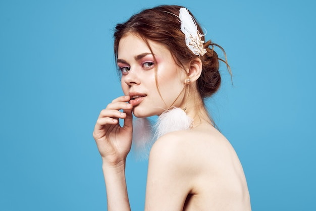 きれいな女性の装飾明るいメイクの魅力的な外観のクローズアップの青い背景。高品質の写真