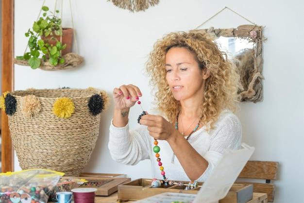 Красивая женщина делает украшения ручной работы дома
