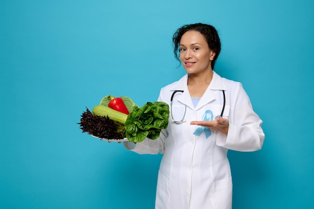 Pretty woman, doctor nutritionist in white medical gown with a blue awareness ribbon shows on plate full of healthy raw vegan eating. world diabetes day concept on colored background with space for ad