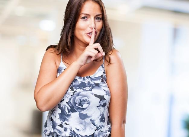 沈黙のジェスチャーをしてきれいな女性
