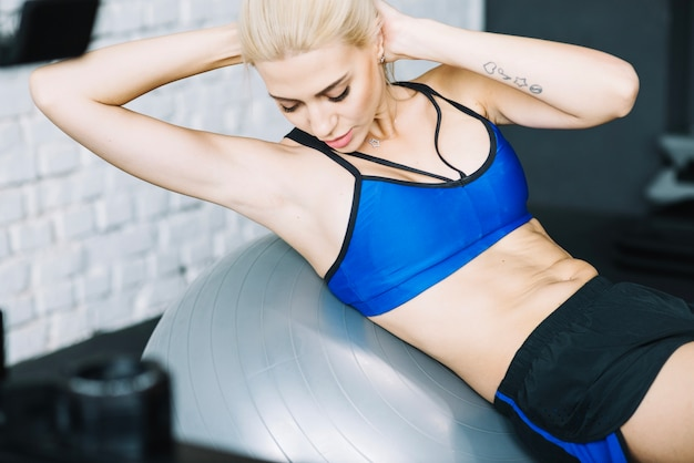 Pretty woman doing abdominal crunches on fitball