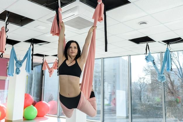 Красивая женщина делает упражнения с гамаком в студии. фитнес для всего для здорового образа жизни. здоровье тела