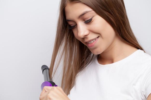 電気アイロンを自宅で髪型をやっているきれいな女性