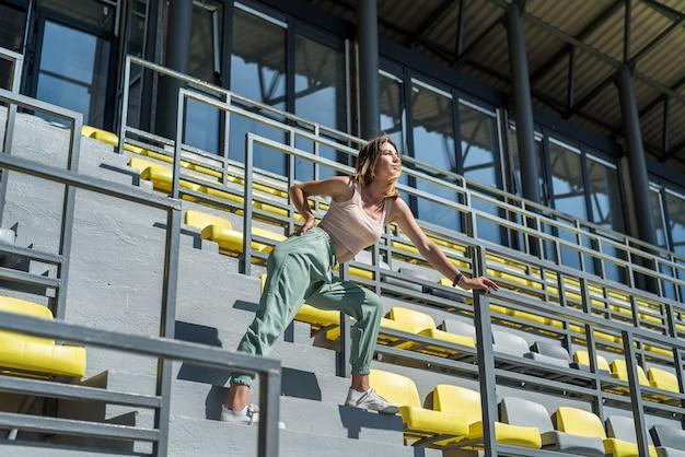 Pretty woman doing relax morning exercises on the stadium tribune