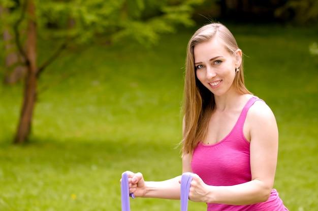 公園の肖像画のクローズアップでヨガの練習をしているきれいな女性