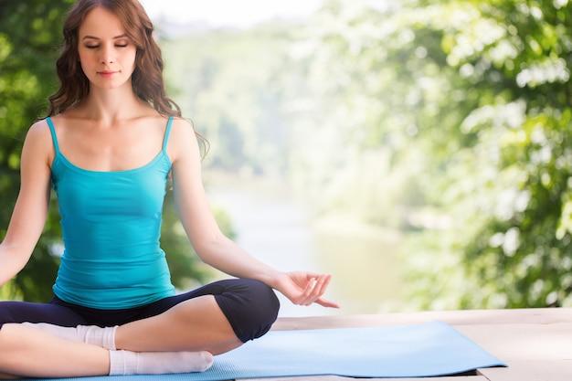 Красивая женщина делает упражнения йоги в парке.