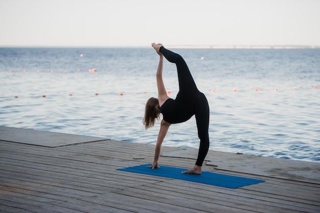 Pretty woman doing yoga at the lake