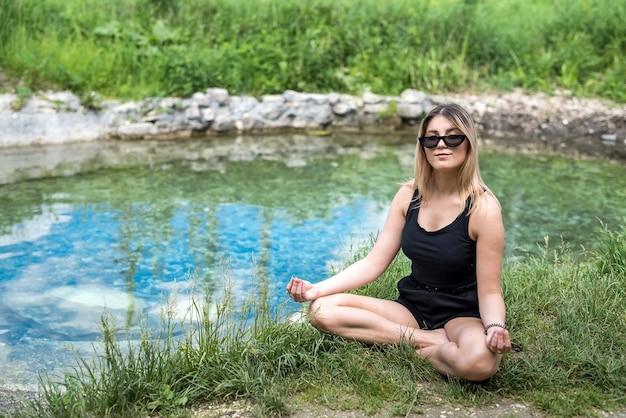 호수 근처, 야외에서 요가 명상을 하 고 예쁜 여자 프리미엄 사진