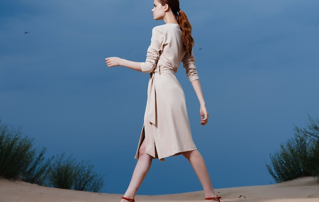 Pretty woman in dress affects nature sand blue sky clouds. high quality photo