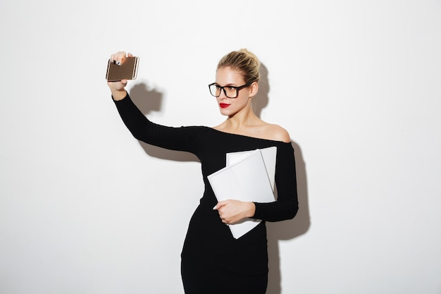 Pretty woman in dress and eyeglasses making selfie on smartphone