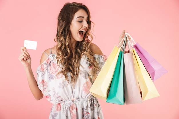 Pretty woman in dress holding credit card and colorful shopping bags, isolated on pink