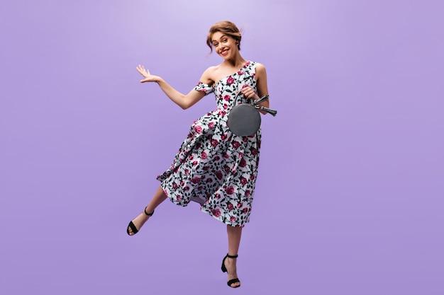 La donna graziosa in vestito tiene la borsa e salta. meravigliosa ragazza con acconciatura alla moda in abiti estivi e scarpe nere sorridenti.